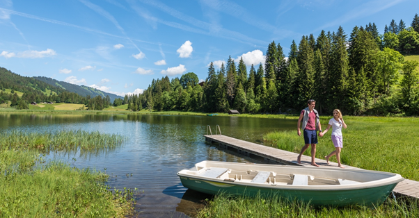 Two people standing on a dock next to a lake  Description automatically generated with low confidence